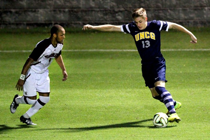 Carolina defender, Ive Burnett, about to steal from Bryan Metz, UNCG #13.