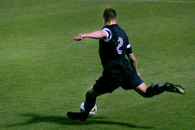 UNCG #2, Aaron Reifschneider, kicking the ball down field.